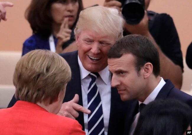 La canciller alemana Angela Merkel (de espaldas) conversa con el presidente de EE.UU. Donald Trump (centro) y con el presidente de Francia Emmanuel Macron, en el primer día de sesiones de la Cumbre del G20, en Hamburgo, Alemania. Julio 7 de 2017.