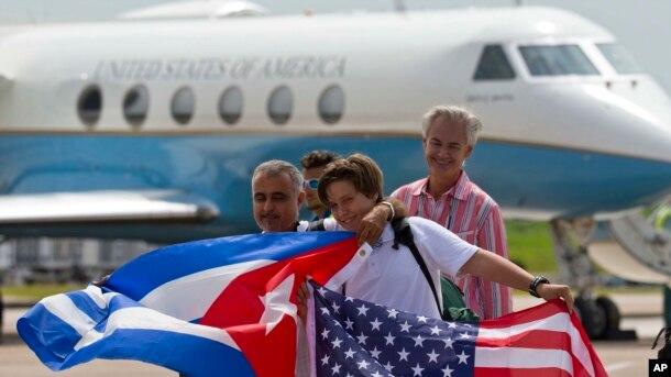 ABŞ təyyarəsi ilə Kubaya səfər etmiş amerikalılar Amerika və Kuba bayraqları ilə