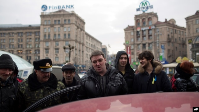 Protesters lsten to ousted President Viktor Yanukovych's press conference on a car radio in Kyiv on Feb. 28, 2014.