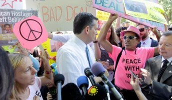 Sen. Ted Cruz, R-Texas, center, talks to a Code Pink member after the antiwar group interrupted his speech during a demonstration in Washington against the proposed Iran nuclear deal because it doesn't address Americans held in Iran, July 23, 2015.