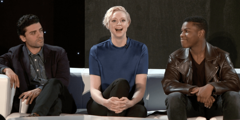Gwendoline Christie reacts to a question, while Oscar Isaac and John Boyega look on.