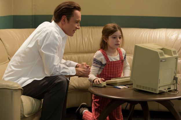 """In this image released by Universal Pictures, Michael Fassbender, left, as Steve Jobs and Makenzie Moss as a young Lisa Jobs, appear in a scene from the film, """"Steve Jobs."""" The movie releases in the U.S. on Friday, Oct. 9, 2015. (Francois Duhamel/Universal Pictures via AP)"""