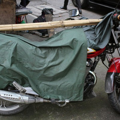 two bamboo poles on top of a motorcycle