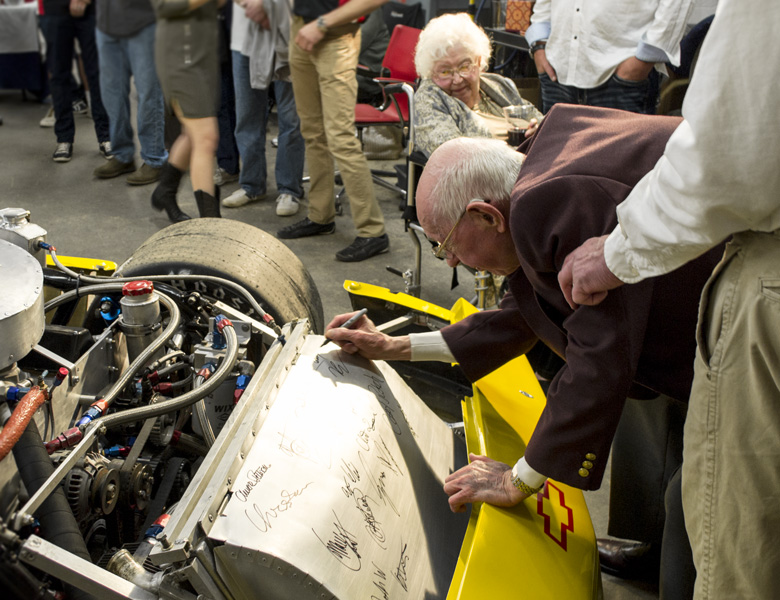 Clay Barfield takes his turn and signs the car during the Genius Garage Open House.