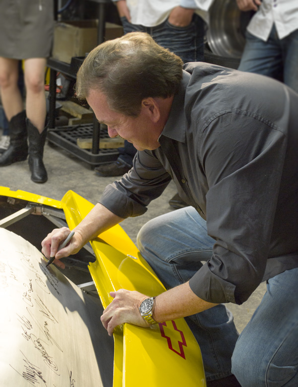 Mervin Dunn, close friend and mentor of the Genius Garage students, signs the car.