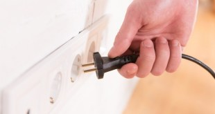 pull the plug concept with man pulling black cord and plug. Close up