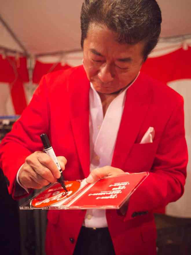 Minami Issei signing a CD for a fan