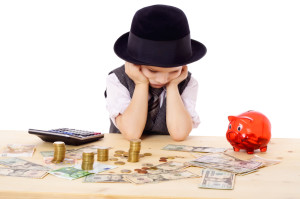Sad boy in black hat at the table with pile of money, isolated on white