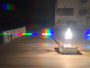 回折分光シートをカメラの前に置いて撮影。 ランプに近い側から、1次回折像、2次回折像、3次回折像とだんだん暗くなっていく回折像が見えます。 2次回折像は、明るく光るフィラメントの回折像にちょうど露出の具合が合っていて、フィラメントの高さに相当した虹の帯が綺麗に観察されますね! 実際は、フィラメントよりも細いスリットを介して撮影して、波長方向の分解能をもう少し高めたもににします。