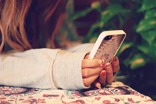 寝転んでスマートフォンを操作する女の子のフリー写真素材(商用可)