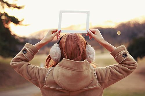 冬の夕焼けの中でフレームを持った女の子のフリー写真素材(商用可)