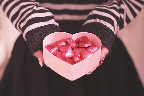バレンタインデーにたくさんのハートチョコを差し出す女の子のフリー写真素材(商用可)