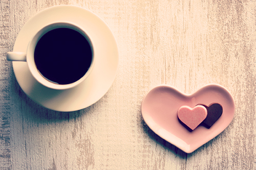 真上から見たブラックコーヒーとハートのチョコレートのフリー写真素材(商用可)