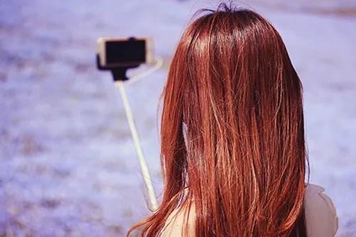 美しい花畑のど真ん中で自撮りをする女の子のフリー写真素材(商用可)