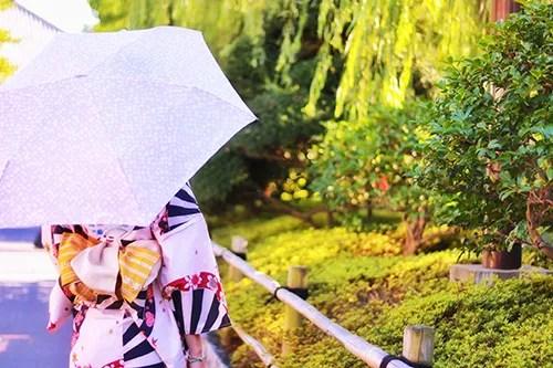 日傘で涼しげに散歩をしている浴衣姿の女の子のフリー写真素材(商用可)