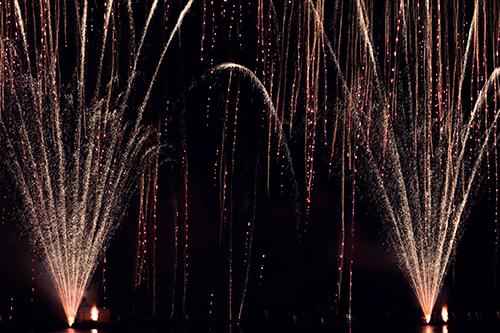 左右から噴き出る花火と空から降り注ぐ花火の共演のフリー写真素材(商用可)