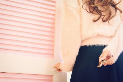 鍵を後ろ手に持っている女の子のフリー写真素材(商用可)