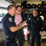 Legislative Fellows Program Lt. Joe Boyatt (Left) and Chief Paul Hartinger (Right) of the Blue Ash Police Department explain the components of various police equipment to Yasar.