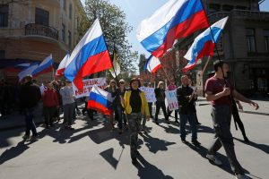 Demonstrators carry Russian flags in support of pro-Russian protesters in eastern Ukraine, in Simferopol, Crimea, Thursday, April 10, 2014. Demonstrators marched and held a rally in support of pro-Russian protesters occupying government buildings in the eastern Ukrainian cities of Donetsk and Luhansk. (AP Photo/Max Vetrov)