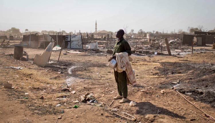 A man carrying his belongings stands amongst the remains of buildings destroyed by  fighting, after government forces on retook the provincial capital of Bentiu, in Unity State, South Sudan, Jan. 12, 2014.  (AP Photo/Mackenzie Knowles-Coursin)