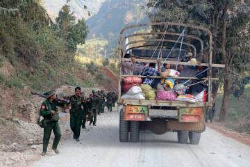 A rescue truck loaded with fleeing locals passes armed military troops near self-administered Kokang capital Laukkai, northern Shan State, Myanmar on Feb. 17, 2015. (EPA/LYNN BO BO)