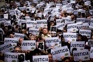 """FILE - In this July 18, 2013 file photo, people hold up signs that read in Spanish: """"Justice"""" and pictures of the victims of the bombing of the Argentine-Israeli Mutual Association community center on the 19th anniversary of the terrorist attack, in Buenos Aires, Argentina. In a statement released Wednesday, Jan. 14, 2015, Argentine Prosecutor Alberto Nisman, who is investigating the 1994 bombing of the Jewish community center, accused President Cristina Fernandez of reaching a deal with Iran to avoid punishing those responsible. (AP Photo/Victor R. Caivano, File)"""