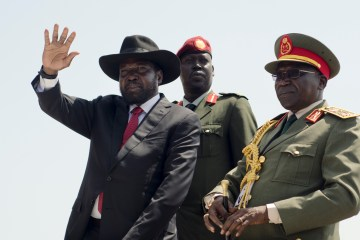 South Sudan's President Salva Kiir, left, accompanied by army chief of staff Paul Malong Awan, right, waves during an independence day ceremony in the capital Juba, South Sudan, Thursday, July 9, 2015. (AP Photo/Jason Patinkin)