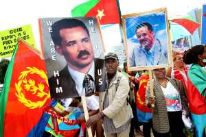 Eritreans in Europe hold pictures of President Isaias Afewerki while protesting  a U.N. Human Rights Council report detailing widespread abuses by the Eritrean government against its own people. (EPA/Magali Girardin)