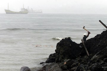 A man does some construction work near the port in Luba, in Equatorial Guinea, August 27, 2002.  (AP Photo/Christine Nesbitt)