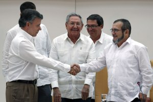 Colombian President Juan Manuel Santos (L) shakes hands with the  top leader of the Revolutionary Armed Forces of Colombia (FARC) Rodrigo Londono 'Timochenko' Echeverri (R) as Cuban President Raul Castro (C) looks on during a press conference announcing a peace agreement in Havana, Sept. 23, 2015.  (EPA/ALEJANDRO ERNESTO)
