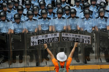 """A protester raises placards that read '""""Occupy Central'"""" and """"'Civil Disobedience'"""" in front of riot policemen outside the government headquarters in Hong Kong, Sept. 27, 2014.   (AP Photo/Vincent Yu)"""