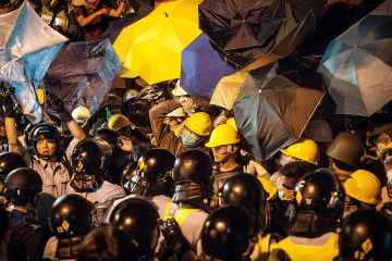 Pro-democracy protesters clash with police outside Hong Kong's Government complex on November 30, 2014 in Hong Kong. Leaders from the Federation of Students called on fellow protesters to attend a rally and come prepared for escalated action. Protesters were asked to bring masks, umbrellas and helmets in a bid to move the protests forward after police successfully cleared the Mong Kok protest site earlier this week.  (Anthony Kwan)