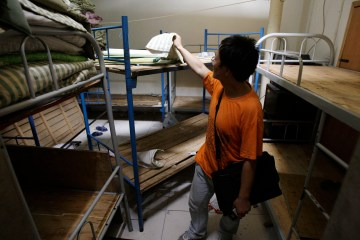 """Blogger and human rights activist Liu Dejun looks through a room in a """"black jail"""" in Beijing where people petitioning the central government from the countryside were held, Aug. 4, 2009. (AP Photo/Greg Baker, File)"""