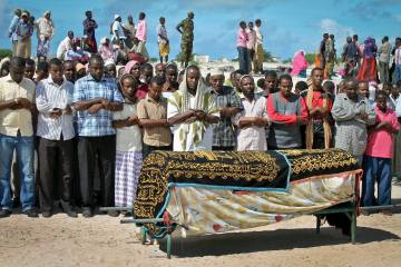 Mourners pray over the body of Somali journalist Mohamed Ibrahim Rage at his funeral April 22, 2013. Rage, who worked for the state-run radio station,  was shot dead by unidentified gunmen in Mogadishu.  (AP Photo/ Farah Abdi Warsameh)