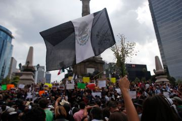 "A person holds up a black Mexican ""mourning"" flag and flowers during a protest over the murder of photojournalist Ruben Espinosa at Mexico City's Angel of the Independence monument, Sunday, Aug. 2, 2015. Mexico City officials said Sunday they are pursuing all lines of investigation into the killing Espinosa and four other women whose bodies were found in the capital, where he had fled from the state of Veracruz because of harassment. According to the Committee to Protect Journalists, 11 journalists have been killed there since 2010, all during the administration of Gov. Javier Duarte. (AP Photo/Dario Lopez-Mills)"