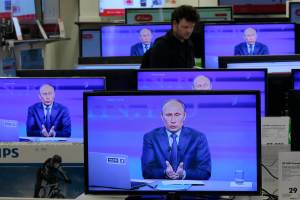 "Russian President Vladimir Putin is seen on television screens in a shop as he speaks during an annual call-in show on Russian television ""Conversation With Vladimir Putin"" in Moscow on April 25, 2013. (AP Photo/Mikhail Metzel)"