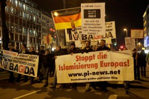 """Participants of BAGIDA, the Bavarian section of the anti-immigration movement 'Patriotic Europeans against the Islamization of the West' (PEGIDA), gather in Munich, Germany, Jan. 19, 2015. The top banner reads: """"You are the negative pressure of democracy, opinion and freedom,"""" bottom, """"Stop the Islamization of Europe.""""  (AP Photo/Matthias Schrader)"""