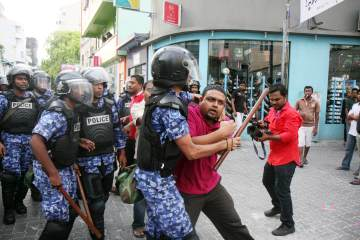 Maldivian police officers detain a journalist during a protest in Male, Maldives, Sunday, May. 01, 2011. Maldives' police have used tear gas and batons to break up a protest demanding that President Mohamad Nasheed step down. Dozens of people have been arrested.(AP Photo/Sinan Hussain)