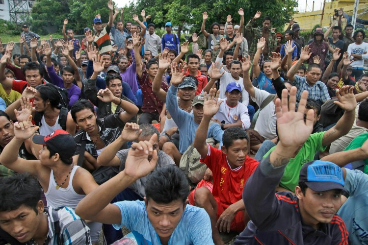 Burmese fishermen raise their hands as they are asked who among them wants to go home at the compound of Pusaka Benjina Resources in Benjina, Indonesia, Friday, April 3, 2015. (AP Photo/Dita Alangkara)