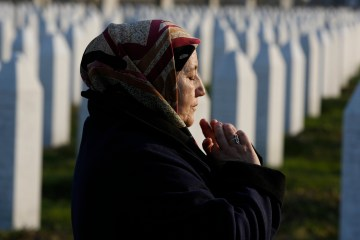 In this photo taken on Sunday, March 20, 2016, Fadila Efendic  prays near the graves of her husband Hamed and son Fejzo, at Memorial Centre Potocari near Srebrenica, Bosnia and Herzegovina.  (AP Photo/Amel Emric)