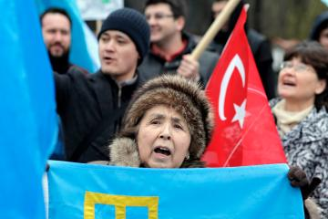 epa05183630 An ethnic Tatar woman from Romania shouts anti Russian slogans and waves a Tatar flag during a protest in support for the Crimean Tatar community that took place in front of the Russian Federation Embassy, in Bucharest, Romania, 27 February 2016. Tenth of ethnic Tatars from Constanta and Bucharest counties, organized by the Democratic Union of Turkish-Muslim Tartars in Romania, gathered near the Russian embassy headquarters to protest against the Russian administration in Crimea, accusing serious rights violations of the Tatar community living in Crimea.  EPA/ROBERT GHEMENT