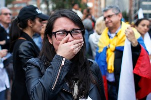 A supporter of the peace accord signed between the Colombian government and rebels of the Revolutionary Armed Forces of Colombia, FARC, cries as she follows on a giant screen the results of a referendum to decide whether or not to support the deal in Bogota, Colombia, Oct. 2, 2016. (AP Photo/Ariana Cubillos)