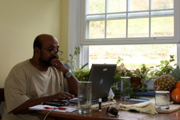Berhanu Nega works on his computer in the kitchen of his house in Lewisburg, Pa., in 2009. Ethiopia sentenced him to death in absentia that year for allegedly supporting a coup to overthrow the government. (AP Photo/John Zeedick)