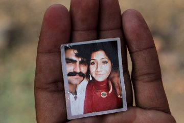 """Mohammed Tofeeq dispalys a picture of himself with his wife Muqadas Tofeeq, who local police say was killed by her mother, at his home in Butrawala village on the outskirts of Gujranwala, Pakistan, Saturday, June 18, 2016. Police in Pakistan say they have arrested the mother of Muqadas Tofeeq who is accused of killing her pregnant daughter for marrying against the wishes of her family. Violence against women is not uncommon in Pakistan where nearly 1,000 women are killed each year in so-called """"honor killings"""" for violating conservative norms on love and marriage. (AP Photo/K.M. Chaudary)"""