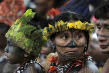 Indians from the tribe Munduruku attend a meeting with the government at the Planalto presidential palace in Brasilia, Brazil,  June 4, 2013. The Indians, who had been occupying the controversial Belo Monte dam which is being built in the Amazon on the Xingu River, were flown to Brasilia by the government for talks to try to end the occupation. Environmentalists and indigenous groups say the dam would devastate wildlife and the livelihoods of thousands of people who live in the area to be flooded. (AP Photo/Eraldo Peres)