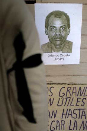 An image of Cuban dissident Orlando Zapata Tamayo hangs on a wall during a vigil in Havana, after his death in 2010. (AP Photo/Franklin Reyes)