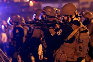 In this Aug. 17, 2014, file photo, police advance after tear gas was used to disperse a crowd during a protest for Michael Brown, who was killed by a police officer in Ferguson, Mo. (AP Photo/Charlie Riedel)