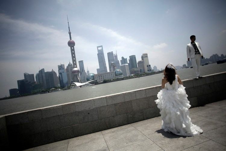 A newlywed couple waits for a wedding photo session in Shanghai in 2012. (AP Photo/Eugene Hoshiko)