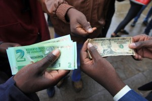 Zimbabweans compare the new note with the US dollar note following the introduction of new notes by the Reserve Bank of Zimbabwe in Harare, Monday, Nov, 28, 2016. (AP Photo/Tsvangirayi Mukwazhi)
