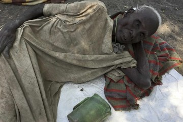 Juang Gai Vol, 87, who hadn't eaten for three days, lies down at a food distribution site in Padeah, South Sudan, March 1, 2017. South Sudanese who fled famine and fighting in Leer county emerged from South Sudan's swamps after months in hiding to receive food aid being distributed by the World Food Program. (AP Photo/Sam Mednick)